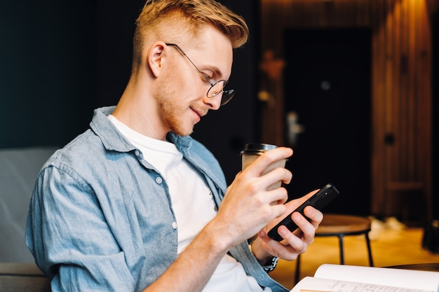 Молодой кавказский человек в очках с помощью мобильного телефона и пить кофе