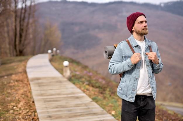 Молодой кавказский человек на природе, глядя в сторону, наслаждаясь пейзажами, пейзажами