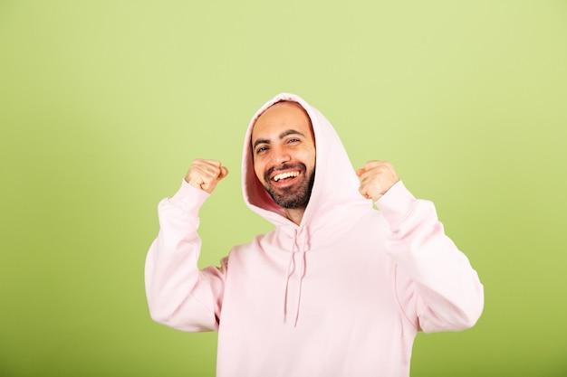 ピンクのパーカーで孤立した、勝者のジェスチャーの成功と幸せな握りこぶしの若い白人男性