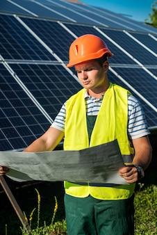 제복을 입은 젊은 백인 남자는 태양광 발전소에서 일합니다. 녹색 에너지의 개념
