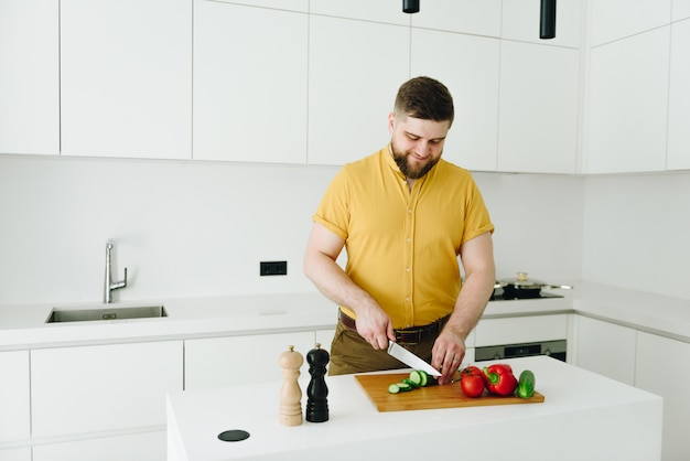 健康的な野菜の食事やナイフを笑顔で白いモダンなキッチンでサラダを調理する黄色のtシャツの若い白人男性