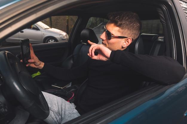 スマートフォンを使用して車の中で若い白人男性