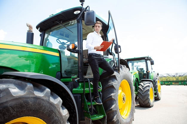 Молодой кавказец, инвестор, покупатель с документами на трактор, комбайн во время работы. смотрится уверенно, яркими летними красками, солнечным светом. сельское хозяйство, выставка, техника, продажа растительной продукции