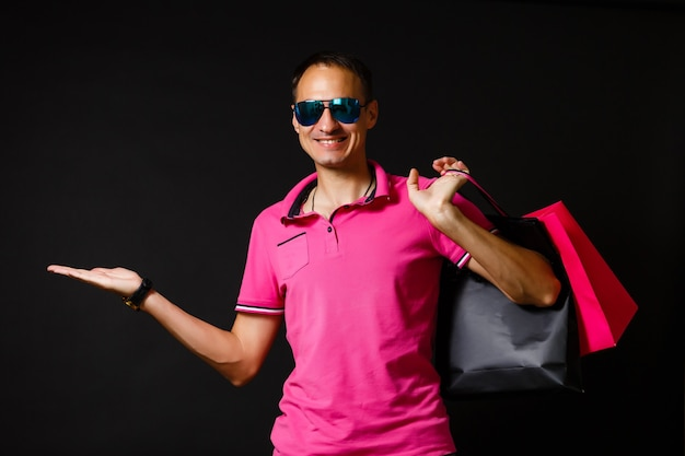 Young caucasian man is holding shopping bags