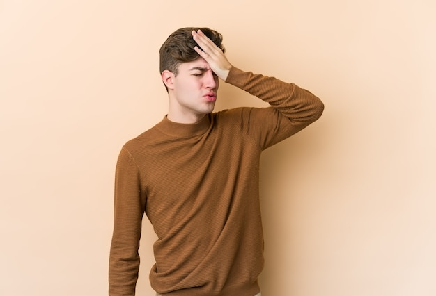 Young caucasian man isolated on beige wall forgetting something, slapping forehead with palm and closing eyes.