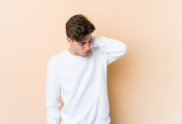 Young caucasian man isolated on beige wall having a neck pain due to stress, massaging and touching it with hand.