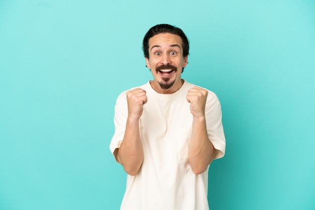 Young caucasian man isolated on blue background celebrating a victory in winner position