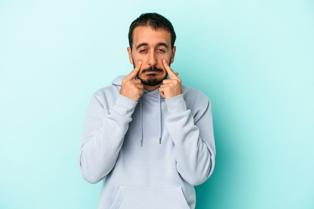 Young caucasian man isolated on blue background crying, unhappy with something, agony and confusion concept.