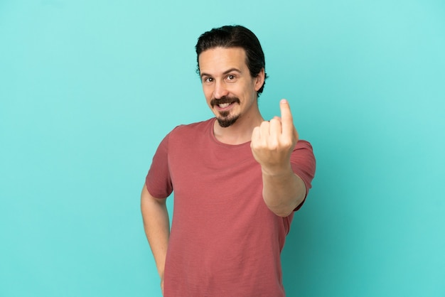 Young caucasian man isolated on blue background doing coming gesture