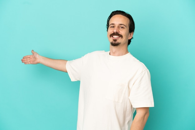 Young caucasian man isolated on blue background extending hands to the side for inviting to come