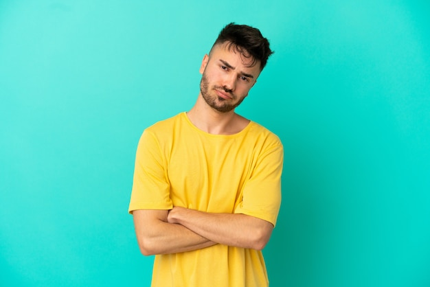 Young caucasian man isolated on blue background feeling upset