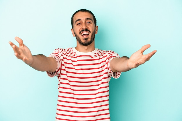 Young caucasian man isolated on blue background feels confident giving a hug to the camera.