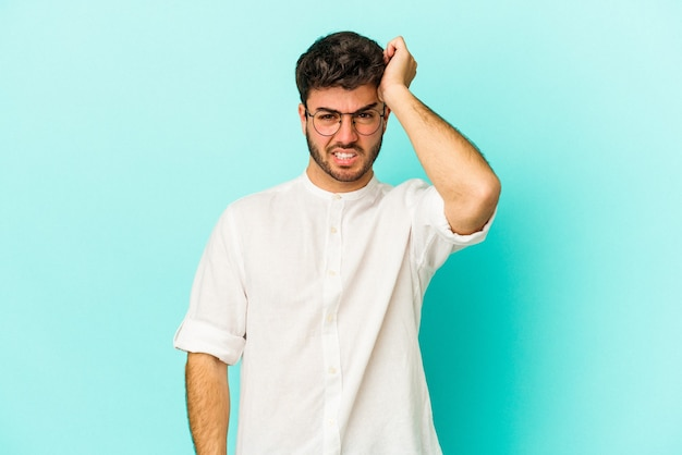 Young caucasian man isolated on blue background forgetting something, slapping forehead with palm and closing eyes.