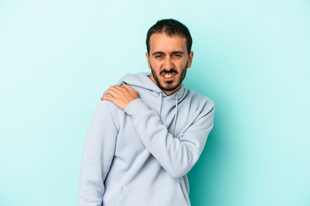 Young caucasian man isolated on blue background having a shoulder pain.