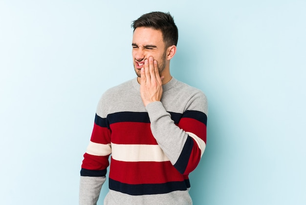 Young caucasian man isolated on blue background having a strong teeth pain, molar ache.