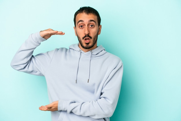 Young caucasian man isolated on blue background holding something with both hands, product presentation.