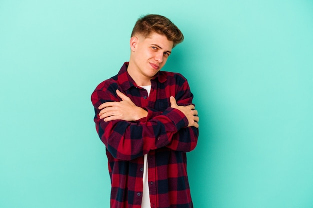 Young caucasian man isolated on blue background hugs, smiling carefree and happy.