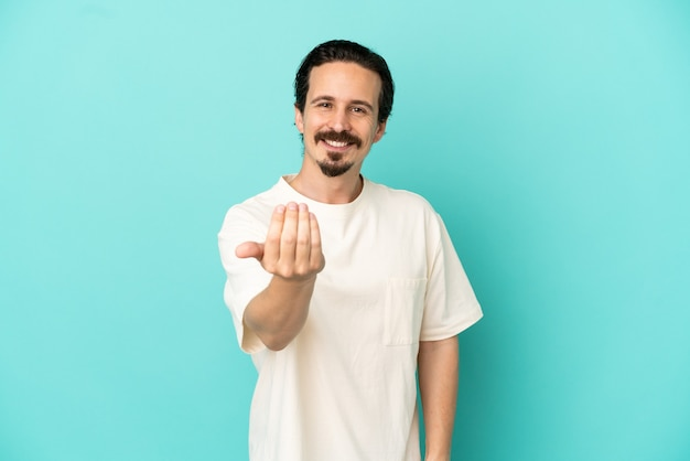 Young caucasian man isolated on blue background inviting to come with hand. happy that you came
