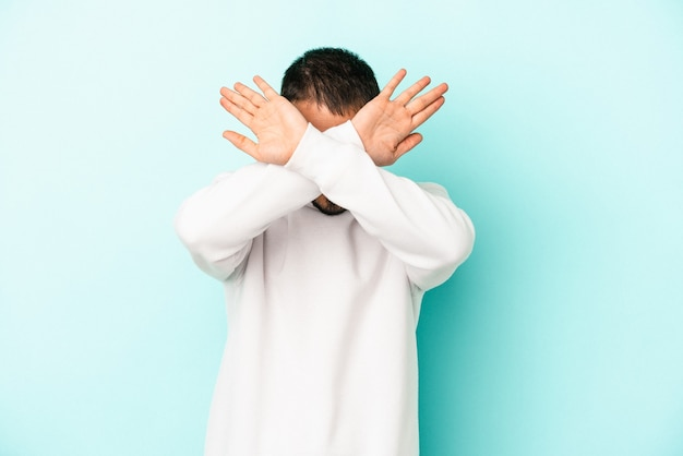 Young caucasian man isolated on blue background keeping two arms crossed, denial concept.