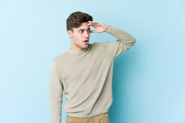 Young caucasian man isolated on blue background looking far away keeping hand on forehead.