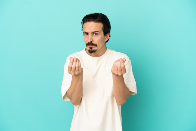 Young caucasian man isolated on blue background making money gesture but is ruined