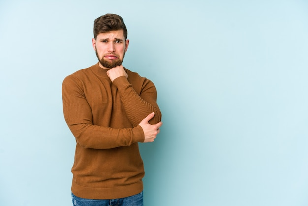 Young caucasian man isolated on blue background massaging elbow, suffering after a bad movemont.