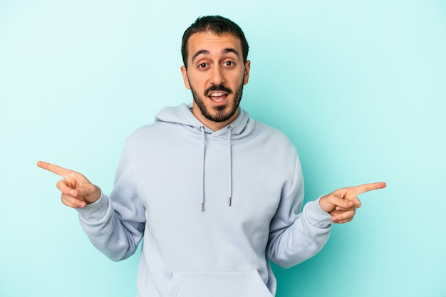 Young caucasian man isolated on blue background pointing to different copy spaces, choosing one of them, showing with finger.