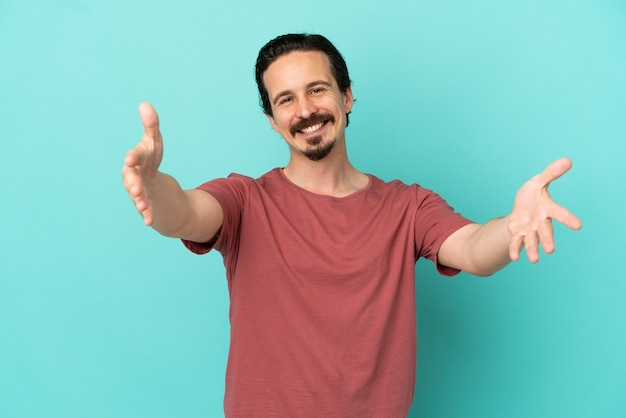 Young caucasian man isolated on blue background presenting and inviting to come with hand