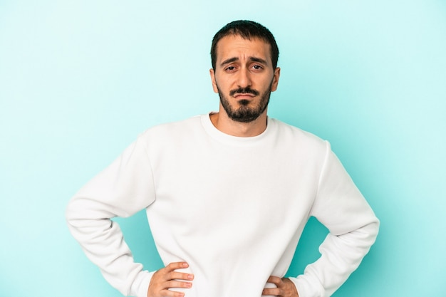 Young caucasian man isolated on blue background sad, serious face, feeling miserable and displeased.