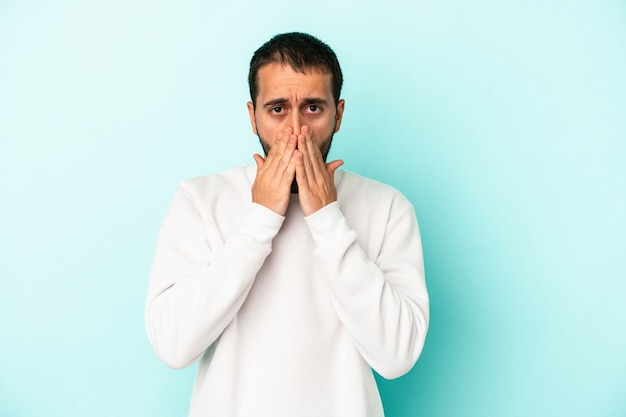Young caucasian man isolated on blue background shocked, covering mouth with hands, anxious to discover something new.