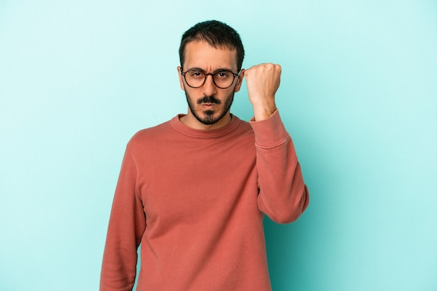 Young caucasian man isolated on blue background showing fist to camera, aggressive facial expression.