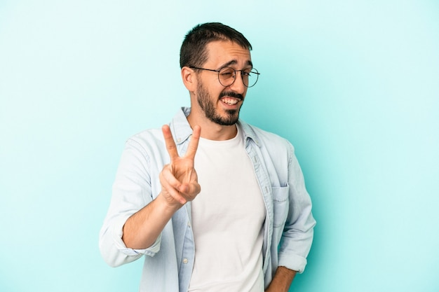 Young caucasian man isolated on blue background showing number two with fingers.