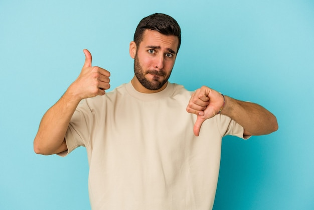 Young caucasian man isolated on blue background showing thumbs up and thumbs down, difficult choose concept