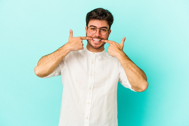 Young caucasian man isolated on blue background smiles, pointing fingers at mouth.