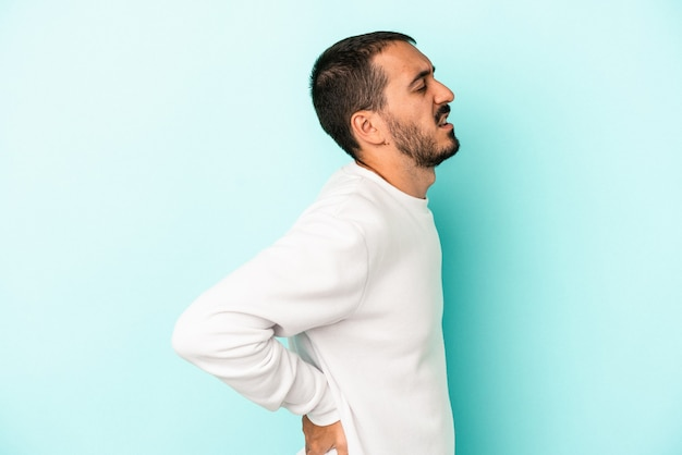 Young caucasian man isolated on blue background suffering a back pain.