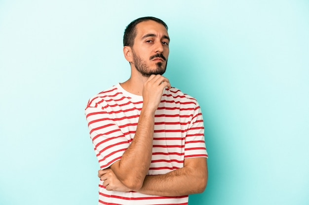 Young caucasian man isolated on blue background suspicious, uncertain, examining you.