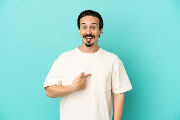Young caucasian man isolated on blue background with surprise facial expression