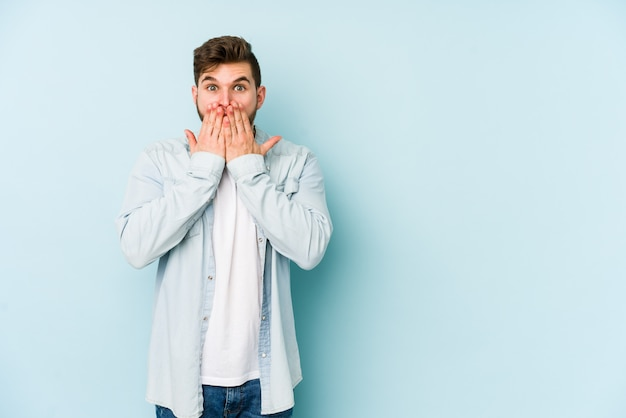 Young caucasian man isolated on blue shocked, covering mouth with hands, anxious to discover something new.