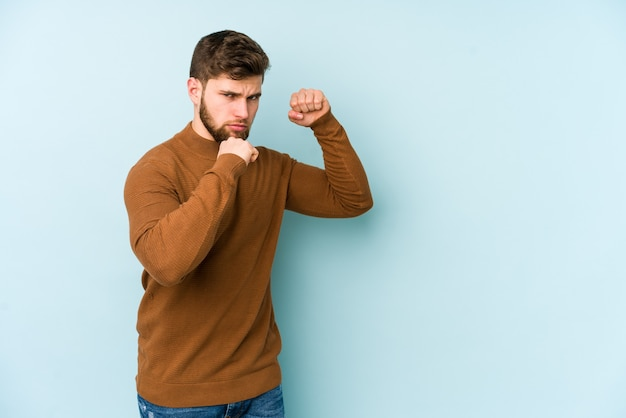 Young caucasian man isolated on blue space throwing a punch, anger, fighting due to an argument, boxing.