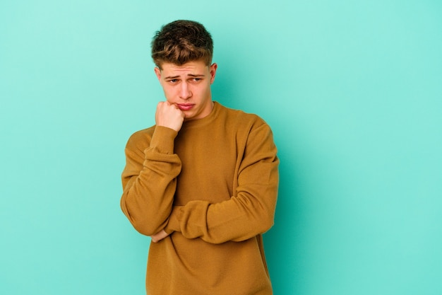 Young caucasian man isolated on blue wall biting fingernails, nervous and very anxious.