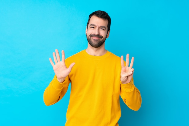 Young caucasian man over isolated blue wall counting eight with fingers