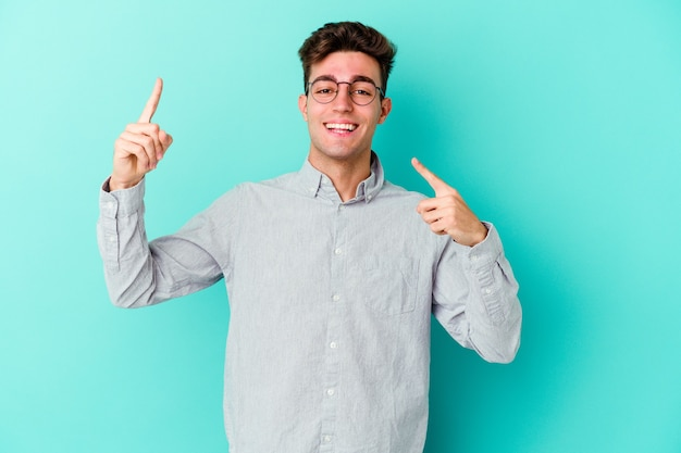 Young caucasian man isolated on blue wall dancing and having fun.
