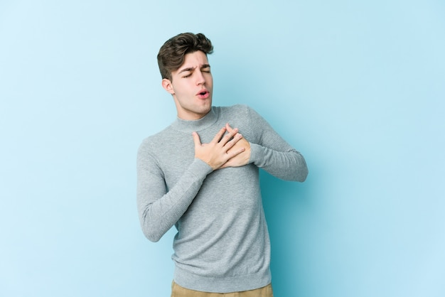 Young caucasian man isolated on blue wall has friendly expression, pressing palm to chest. love concept.