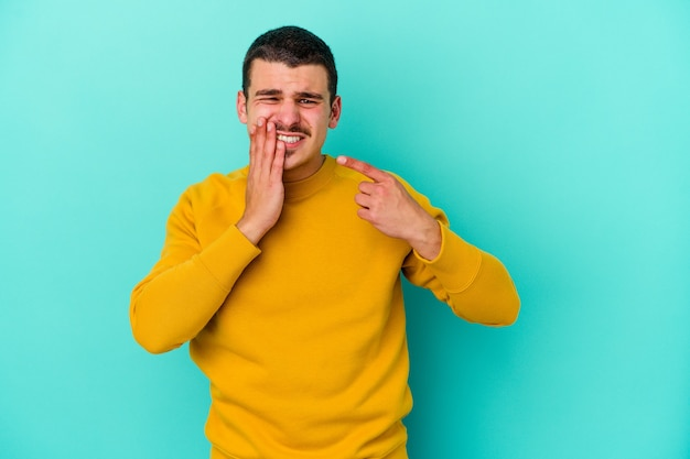 Young caucasian man isolated on blue wall having a strong teeth pain, molar ache.