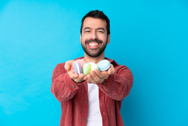 Young caucasian man over isolated blue wall holding colorful french macarons