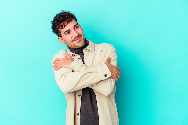 Young caucasian man isolated on blue wall hugs, smiling carefree and happy.