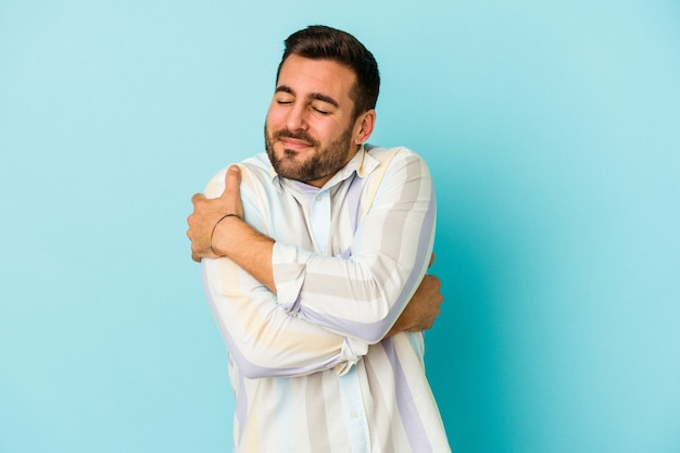 Young caucasian man isolated on blue wall hugs, smiling carefree and happy