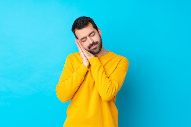 Young caucasian man over isolated blue wall making sleep gesture in dorable expression