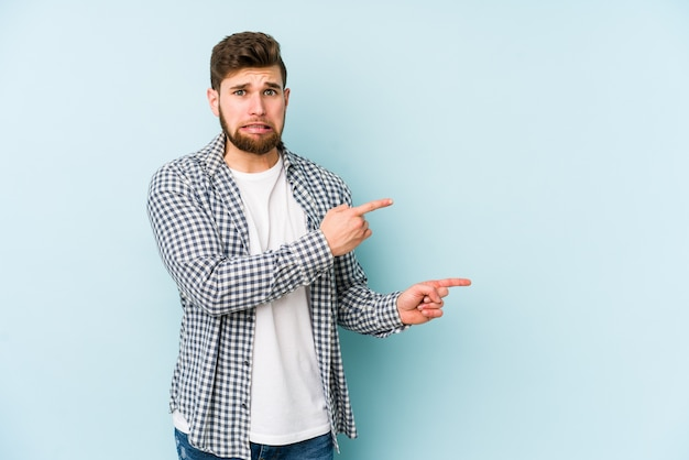 Young caucasian man isolated on blue wall shocked pointing with index fingers to a copy space.