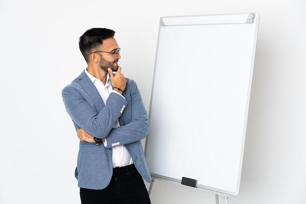 孤立した若い白人男性がホワイトボードと見ている側でプレゼンテーションを行う